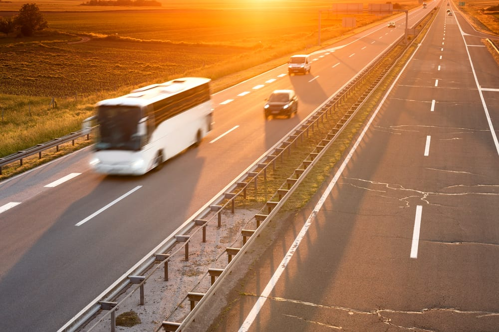 Bus and cars on highway at sunset