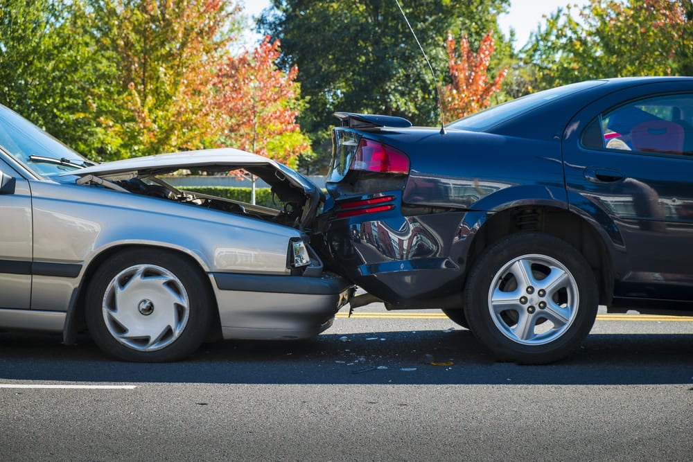 Car crash, fender bender, close-up in front of fall trees