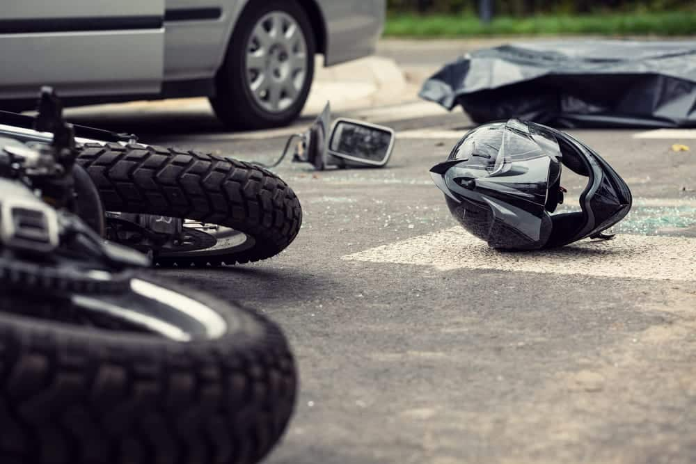 Motorcycle helmet and motorcycle on road after collision