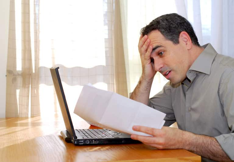 Frustrated man looking at paper, open laptop