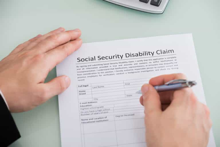 Close-up of hand completing social security disability claim