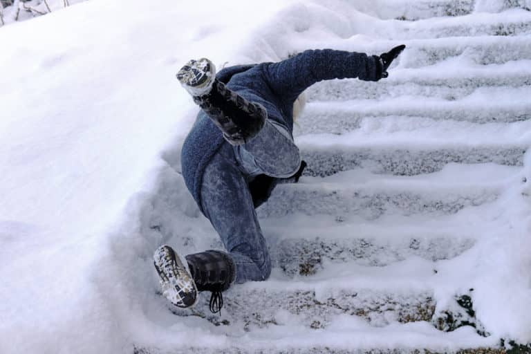 Woman slipping while walking up snowy icy outdoors steps